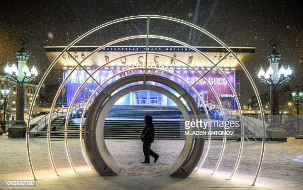 A security guard walks under the snow in front of the Moscow Theatre of Musical decorated for the upcoming holidays in Moscow on December 5 2018