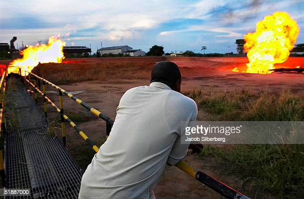 A security guard watches as associated gas produced from oil wells is burned or 'flared' October 9 2004 near Port Harcourt Nigeria The practice of...