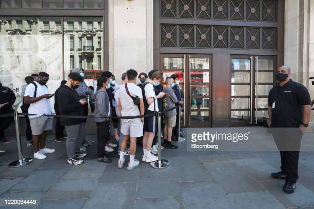 Security guard watches as customers stand in line to enter the Niketown store, operated by Nike Inc., in London, U.K., on Monday, June 15, 2020....