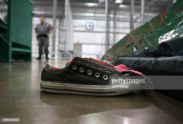 A security guard watches as girls from Central America sleep at a detention facility run by the US Border Patrol on September 8 2014 in McAllen Texas...