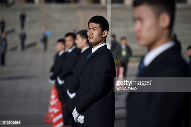 A security guard watches during the 3nd plenary session of the National People's Congress outside the Great Hall of the People in Beijing on March 13...