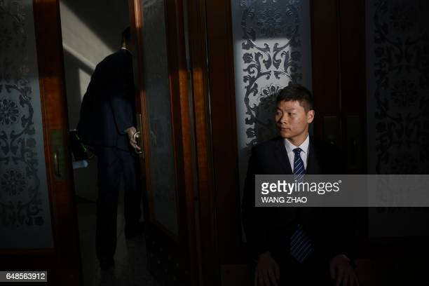 A security guard watches during the Anhui province opening session as part of the National People's Congress at the Great Hall of the People in...