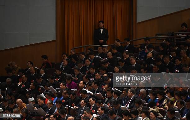 A security guard watches over delegates and guests during the opening session of the National People's Congress in the Great Hall of the People in...