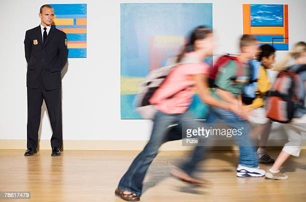 security guard watching elementary students running - bokeh museum stock photos and pictures