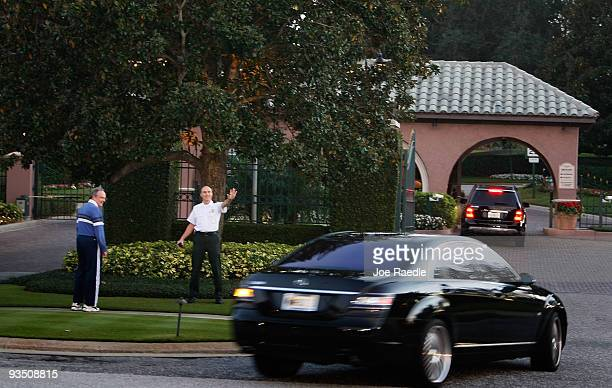A security guard waves as a car drives to an entrance gate to the Isleworth community where Tiger Woods has a home on November 30 2009 in Windermere...