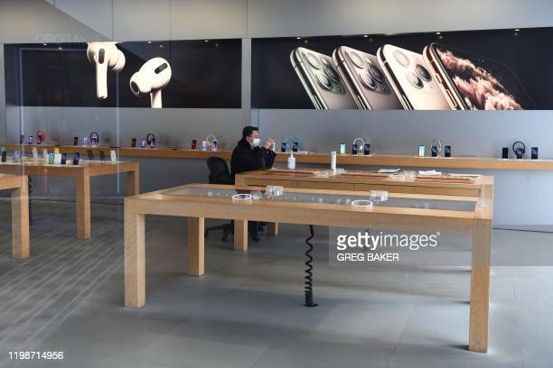 A security guard wearing a face mask looks at his mobile phone in a closed Apple store in Beijing on February 5 2020 China's struggle to contain the...