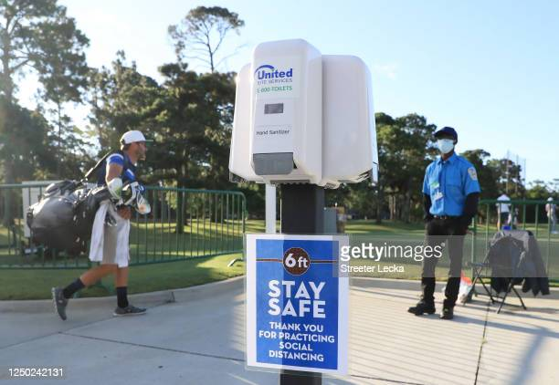 Security guard wearing a face mask looks on near COVID-19 social distancing signage and hand sanitizer at the entrance to the driving range during a...