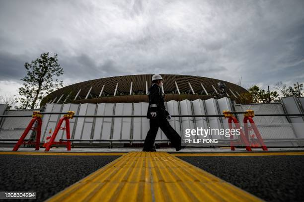 A security guard wearing a face mask walks in front of a construction site at the Japan National Stadium in Tokyo on March 27 three days after the...