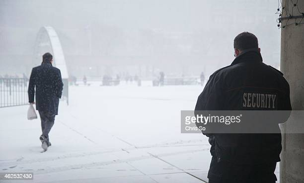 Security guard wearing a G4S uniform takes shelter under an overhang as snow falls on Nathan Phillip's Square. City Hall has bolstered it's staff...