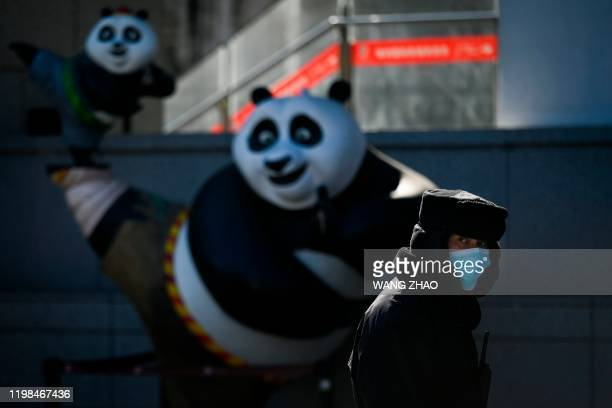 A security guard wearing a mask looks on while walking past a panda statue at the entrance of a cinema in Beijing on February 4 2020 The number of...