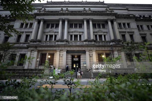 Security guard wearing a protective face mask, left, stands outside the Bank of Japan headquarters in Tokyo, Japan, on Monday, Sept. 14, 2020. The...