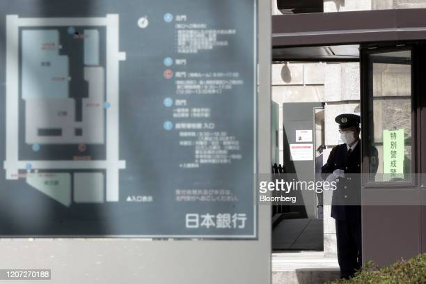Security guard wearing a protective mask stands outside the Bank of Japan headquarters in Tokyo, Japan, on Monday, March 16, 2020. The Bank of Japan...