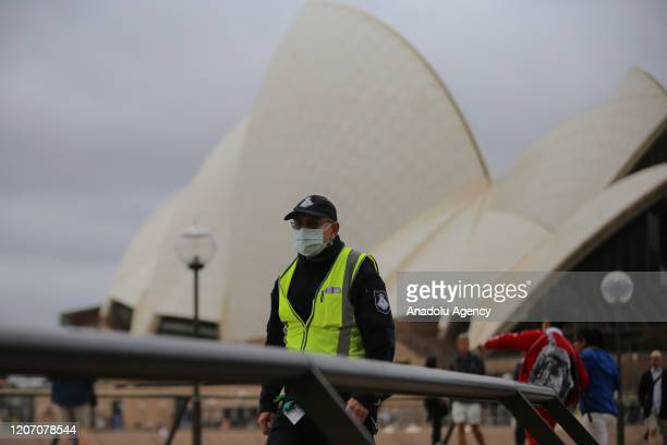 A security guard wears a face mask as a preventative measure against Coronavirus COVID19 in front of the Sydney Opera House in Sydney Australia on...