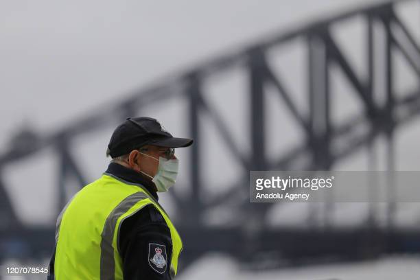 A security guard wears a face mask as a preventative measure against Coronavirus COVID19 in front of the Sydney Harbour Bridge in Sydney Australia on...