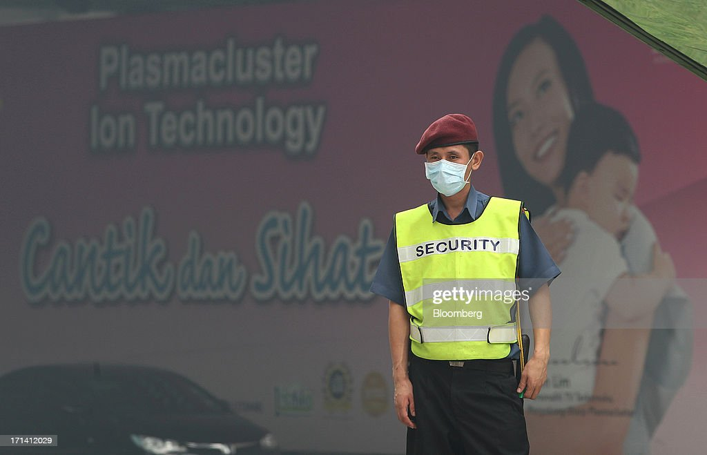 A security guard wears a face mask as he stands guard outside the Lot 10 shopping complex at Bukit Bintang in Kuala Lumpur, Malaysia, on Monday, June 24, 2013. Malaysia called for a meeting of Southeast Asian ministers as early as next week after haze from illegal Indonesian forest fires reached hazardous levels in parts of the region. Photographer: Goh Seng Chong/Bloomberg via Getty Images