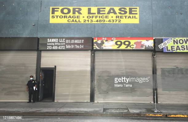 A security guard wears a face mask while standing outside shuttered shops and a 'For Lease' sign amid the global coronavirus pandemic on March 30...