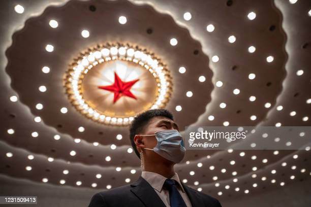 Security guard wears a protective mask as he guards at the opening session of the Chinese People's Political Consultative Conference at the Great...