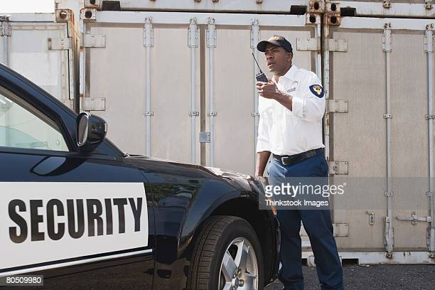 security guard with car and walkie talkie - watchmen stock pictures, royalty-free photos & images