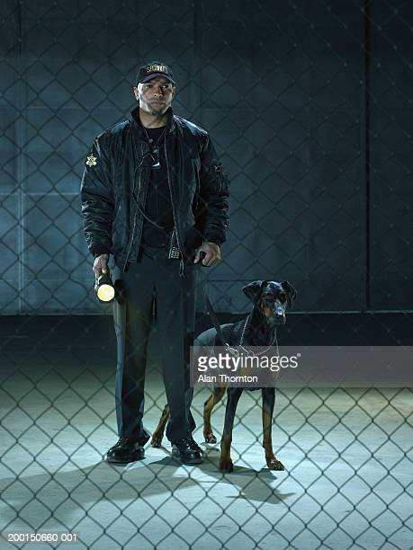 Security guard with dog and torch, view through chain link fence