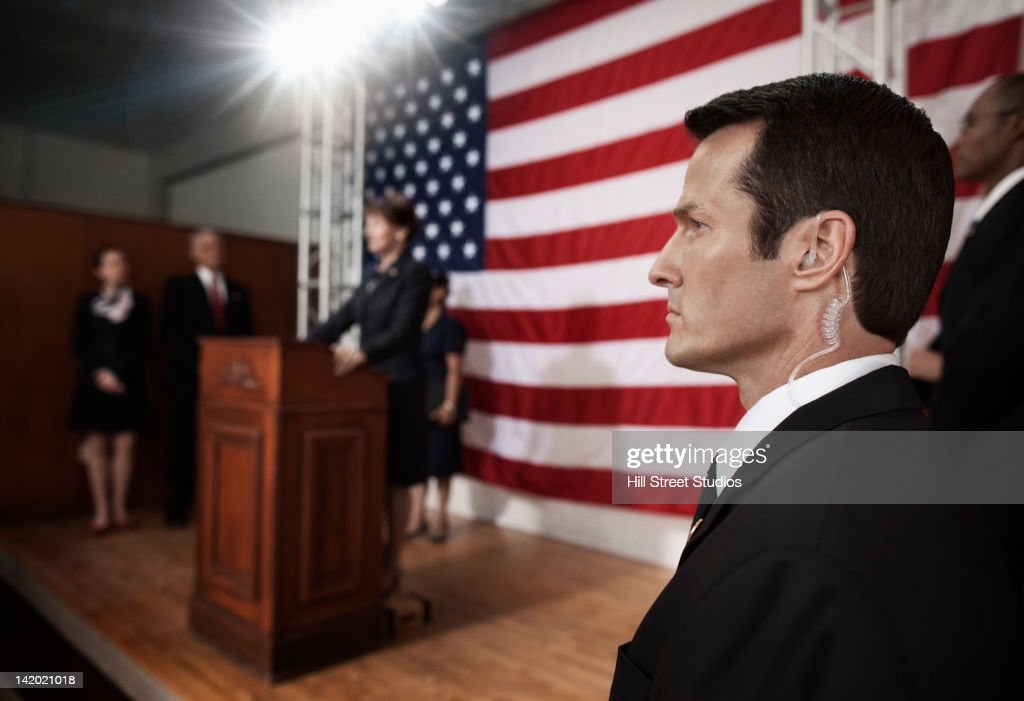 Security guard with earpiece at public speech : Stock Photo