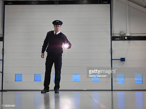 Security guard with torch in warehouse
