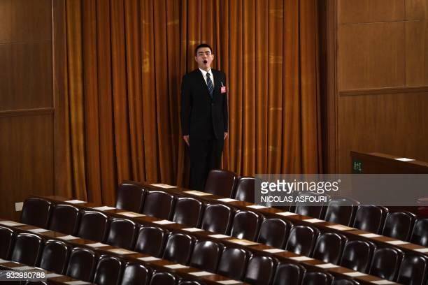 A security guard yawn ahead of the fifth plenary session of the first session of the 13th National People's Congress at the Great Hall of the People...