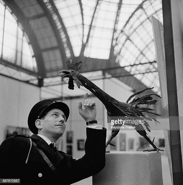 A security guardian points out a sculpture exhibited at the Great Palace at the 76th Independents' exhibition on April 22 1965 in Paris France