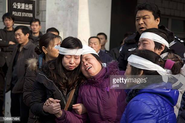 Security guards and policemen block the entrance of Nanyuna police station in Beijing on December 22 2010 as relatives protest outside after Chinese...