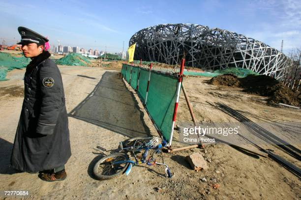 "Security guards at the National Stadium structure, dubbed the ""Bird's Nest"", on December 7, 2006 in Beijing, China. Continuous progress has been made..."