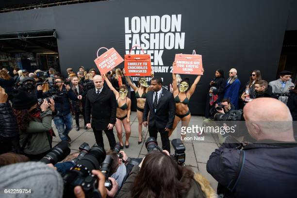 Security guards attempt to block photographers from seeing models wearing lingerie and crocodile masks as they a protest for the PETA animal welfare...
