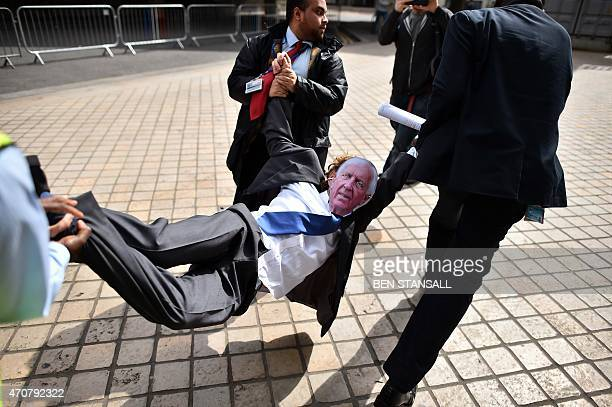 Security guards carry a protester wearing a mask depicting Sir David Walker outgoing Chairman of Barclays Bank during a demonstration outside the...
