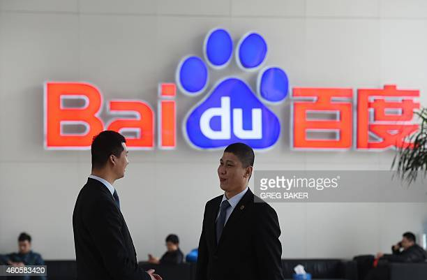 Security guards chat near a Baidu logo at the Baidu headquarters in Beijing on December 17, 2014. Baidu, China's leading search engine, and ride...