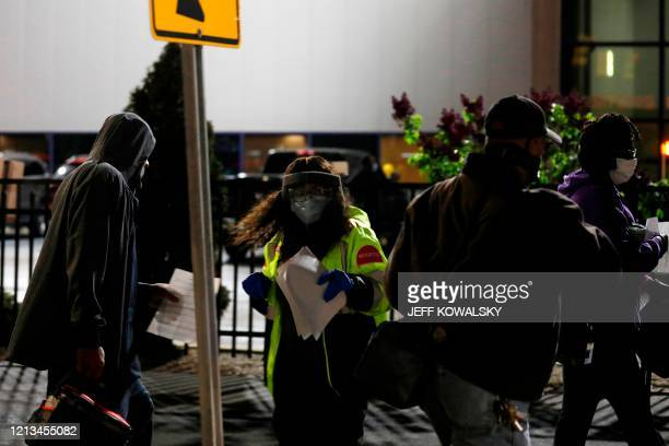 Security guards check the paper work from returning workers as they return to FCA Chrysler Warren Truck Assembly to restart production on May 18,...
