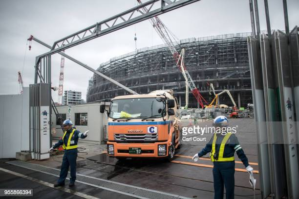 Security guards ensure the road is clear as a truck leaves after making a delivery to the under-construction New National Stadium, the main stadium...