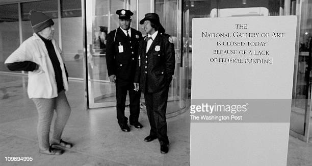 Security guards explain to a visitor that she will not be able to enter the National Gallery of Art because of the federal shutdown