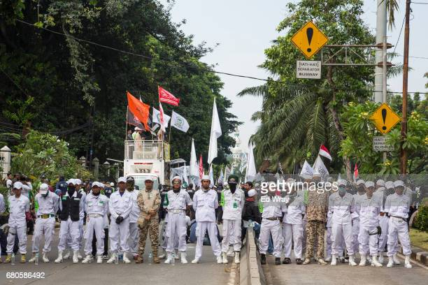 Security guards for the hardline Islamic group FPI face off with police while awaiting the verdict in the trial of Jakarta's Governor on blasphemy...