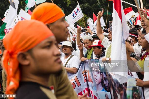 Security guards from an Islamic group keep watch as thousands of Indonesian Muslims demonstrate in support of the Rohingya ethnic group who are being...