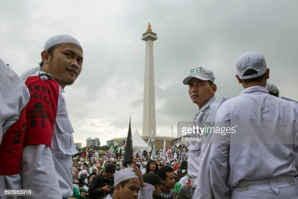 Security guards from the hardline Islamic group Islamic Defenders Front look over a large demonstration against the United States' decision to...