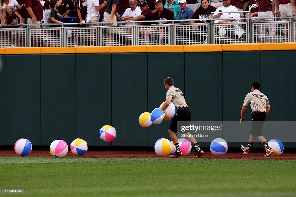 Security guards gather up beachballs that fell out of the right field bleacher crowd between innings as the UCLA Bruins play the Mississippi State Bulldogs during game one of the College World Series Finals on June 24, 2013 at TD Ameritrade Park in Omaha, Nebraska. UCLA won 3-1.
