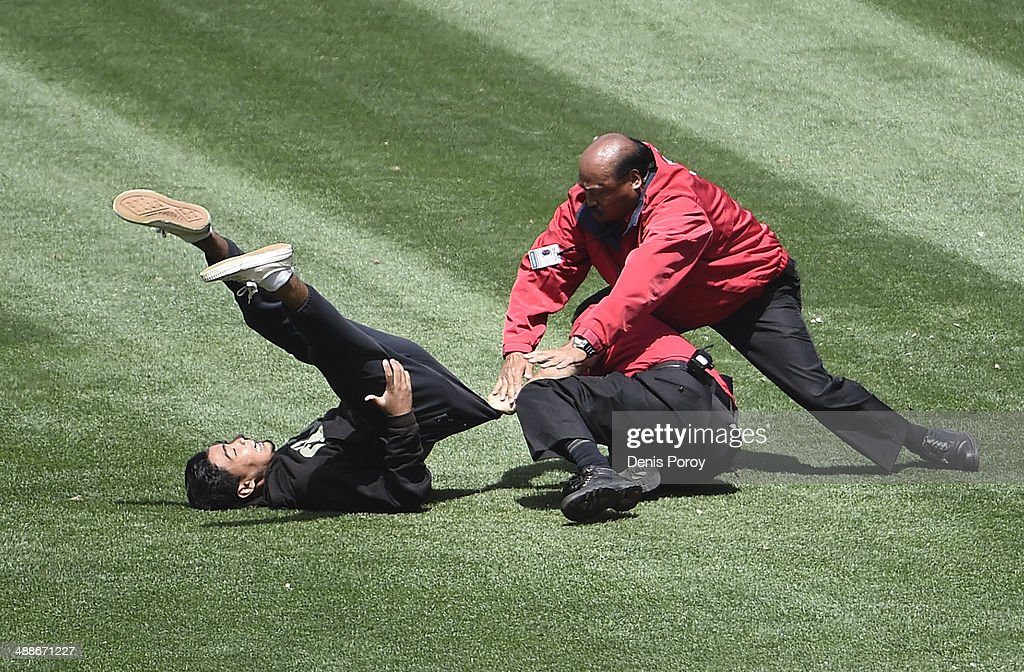 Security guards grab a man who ran onto the field during the fifth inning of a baseball game between San Diego Padres and the Kansas City Royals at Petco Park May 7, 2014 in San Diego, California.