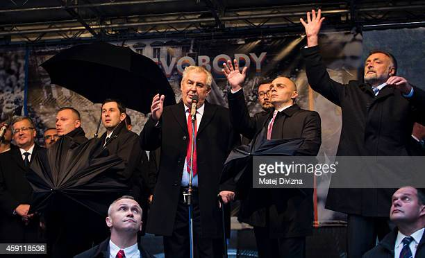 Security guards hide behind umbrellas as people throw eggs and tomatos at the President of Czech Republic, Milos Zeman, during the unveiling of a...