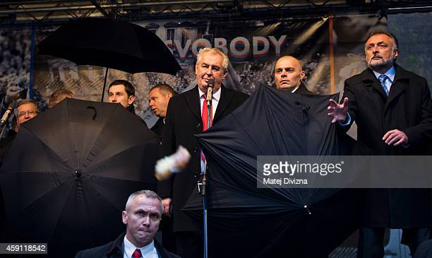 Security guards hide behind umbrellas as people throw eggs and tomatos at the President of Czech Republic Milos Zeman during the unveiling of a...