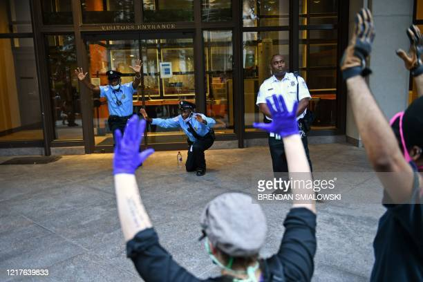 Security guards hold up their arms and kneel down at the IMF heaquarters as protestors pass by during a march near the White House protesting the...