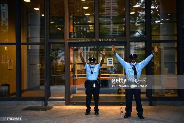 Security guards hold up their arms at the IMF heaquarters as protestors pass by during a march near the White House protesting the death of George...