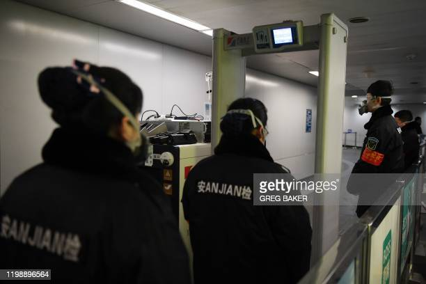 Security guards keep watch as an AIpowered system developed by Chinese tech firm Megvii screens commuters for fevers as they enter the Mudanyuan...
