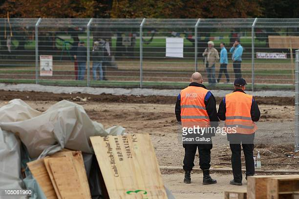 Security guards keep watch as people walk by a security fence at a demolition site at Hauptbahnhof train station once stood on October 8 2010 in...