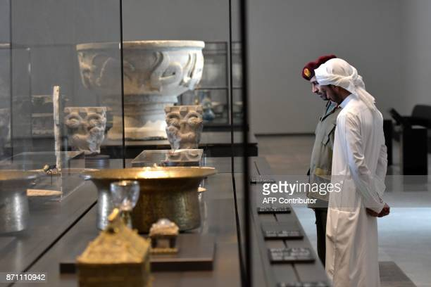 Security guards look at statues on display in a gallery at the Louvre Abu Dhabi Museum during a media tour on November 6, 2017 prior to the official...