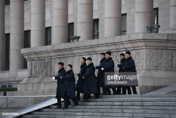 Security guards march down the steps of the Great Hall of the People during the National People's Congress in Beijing on March 7 2017 More than 3000...