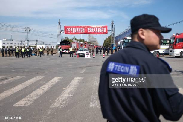 Security guards patrol as police officers block off the road leading to the site of an explosion in Yancheng in China's eastern Jiangsu province on...