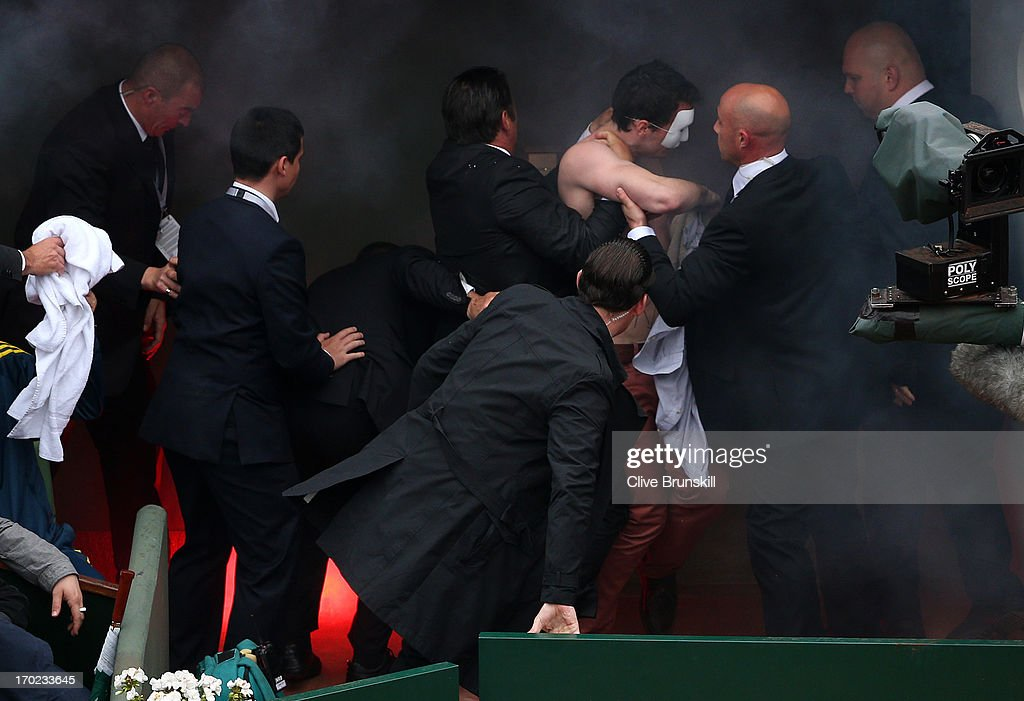 Security guards restrain a protester after he lit a flare and ran on court before the start of a game in the Men's Singles final match between Rafael Nadal of Spain and David Ferrer of Spain during day fifteen of the French Open at Roland Garros on June 9, 2013 in Paris, France.